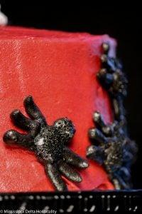 black meringue spiders on the side of a devils food cake