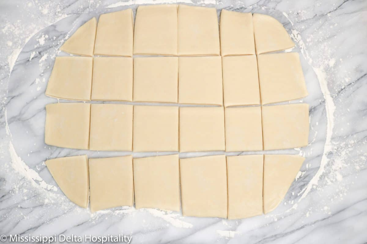 beignet dough cut into 24 squares on a floured marble surface.