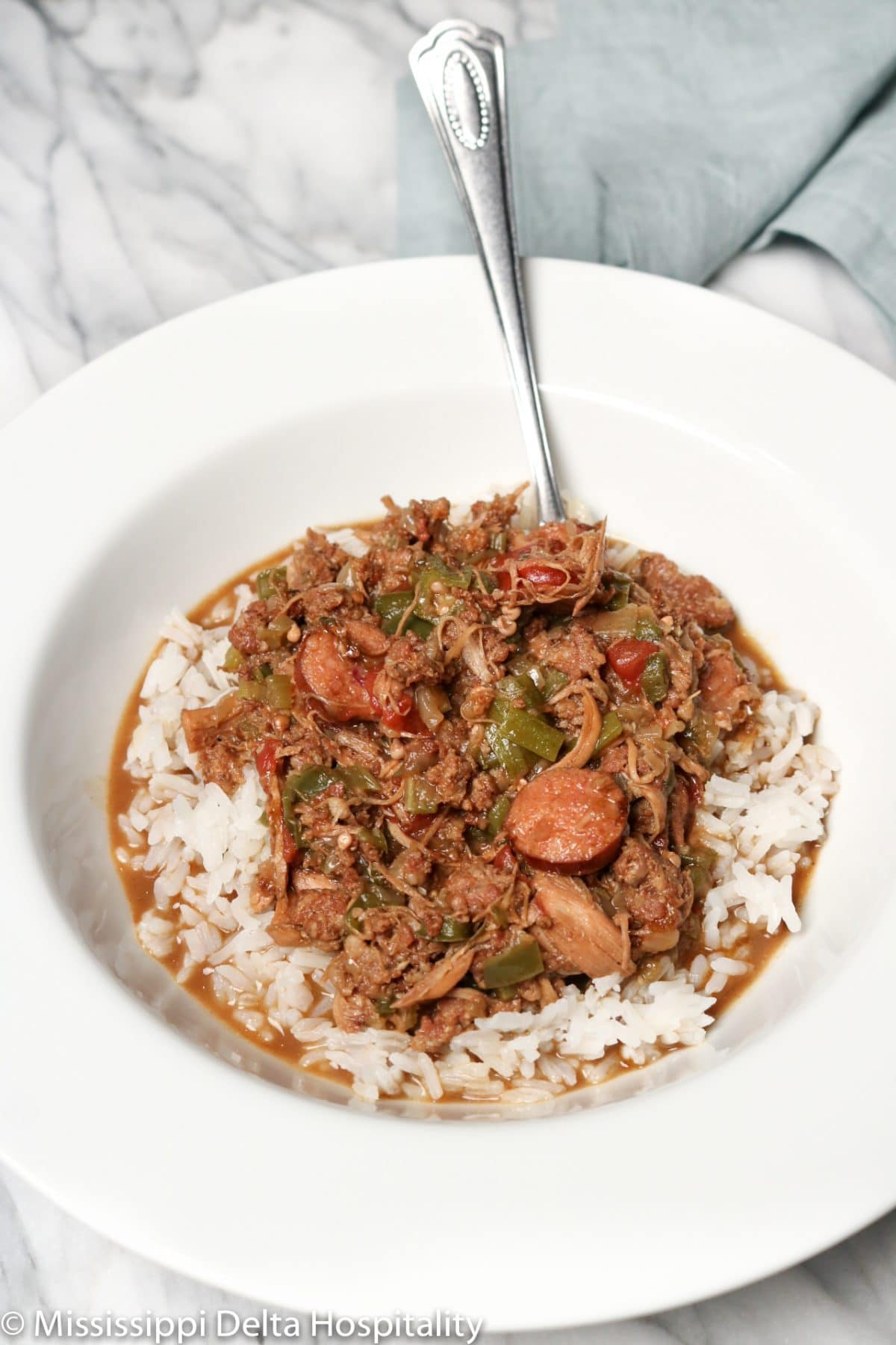 A bowl full of chicken and sausage gumbo with a spoon in it on a marble board with a teal napkin in the background.