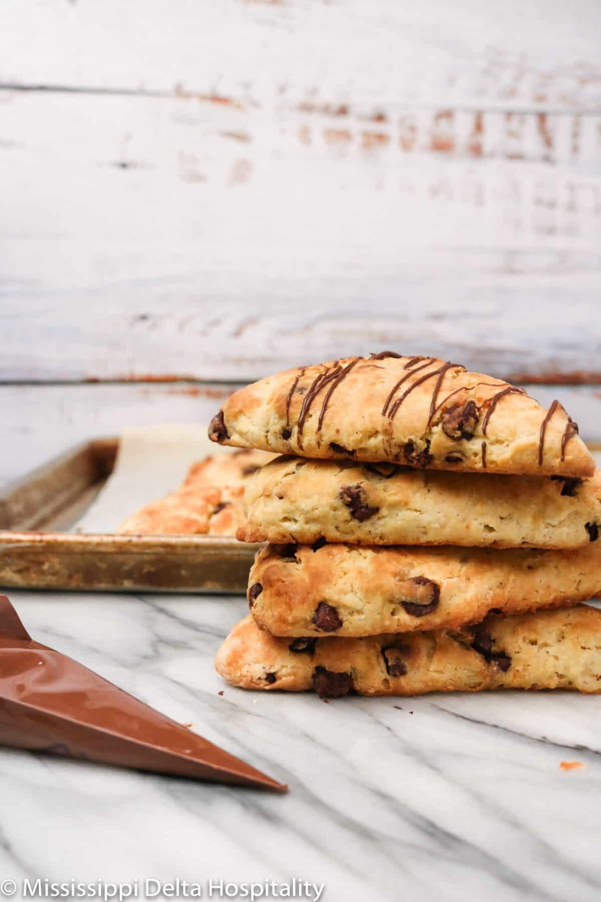 four chocolate chip scones stacked on a marble board with chocolate drizzle.