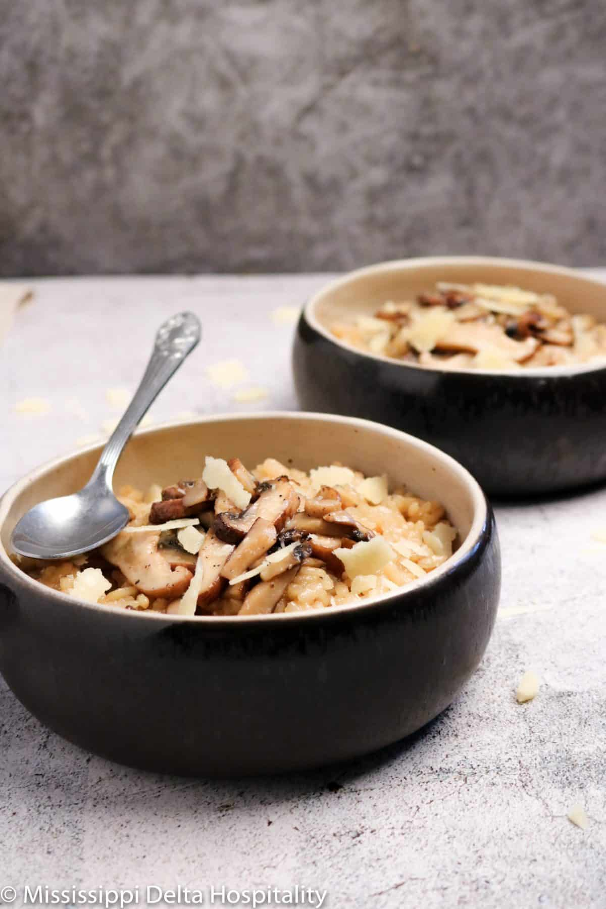 two bowls of mushroom risotto with a silver spoon