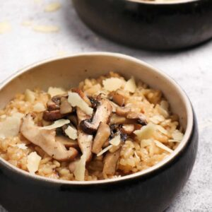 two bowls of mushroom risotto on a concrete board