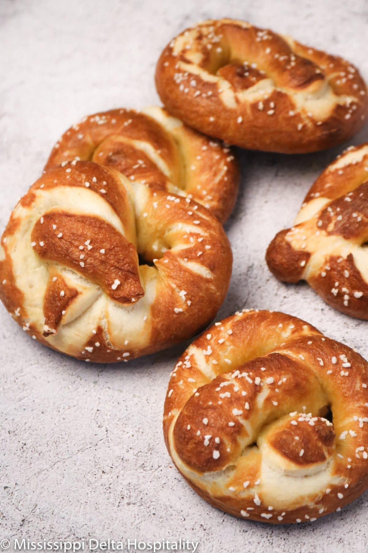 five pretzels laying on a concrete board.