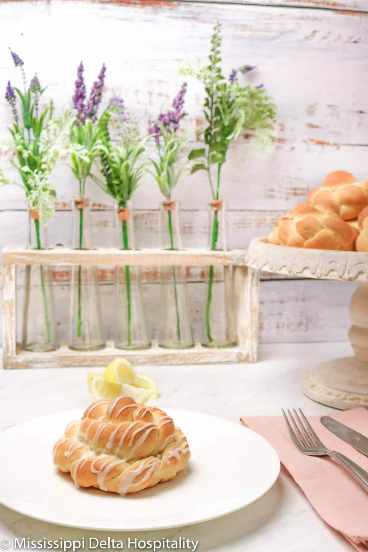 a glazed lemon knot on a white plate with a pink napkin and a fork and knife. In the background is a antiqued cake plate with lemon knots on it with a few small vases of lavender behind it on a marble board and a white washed wood background.