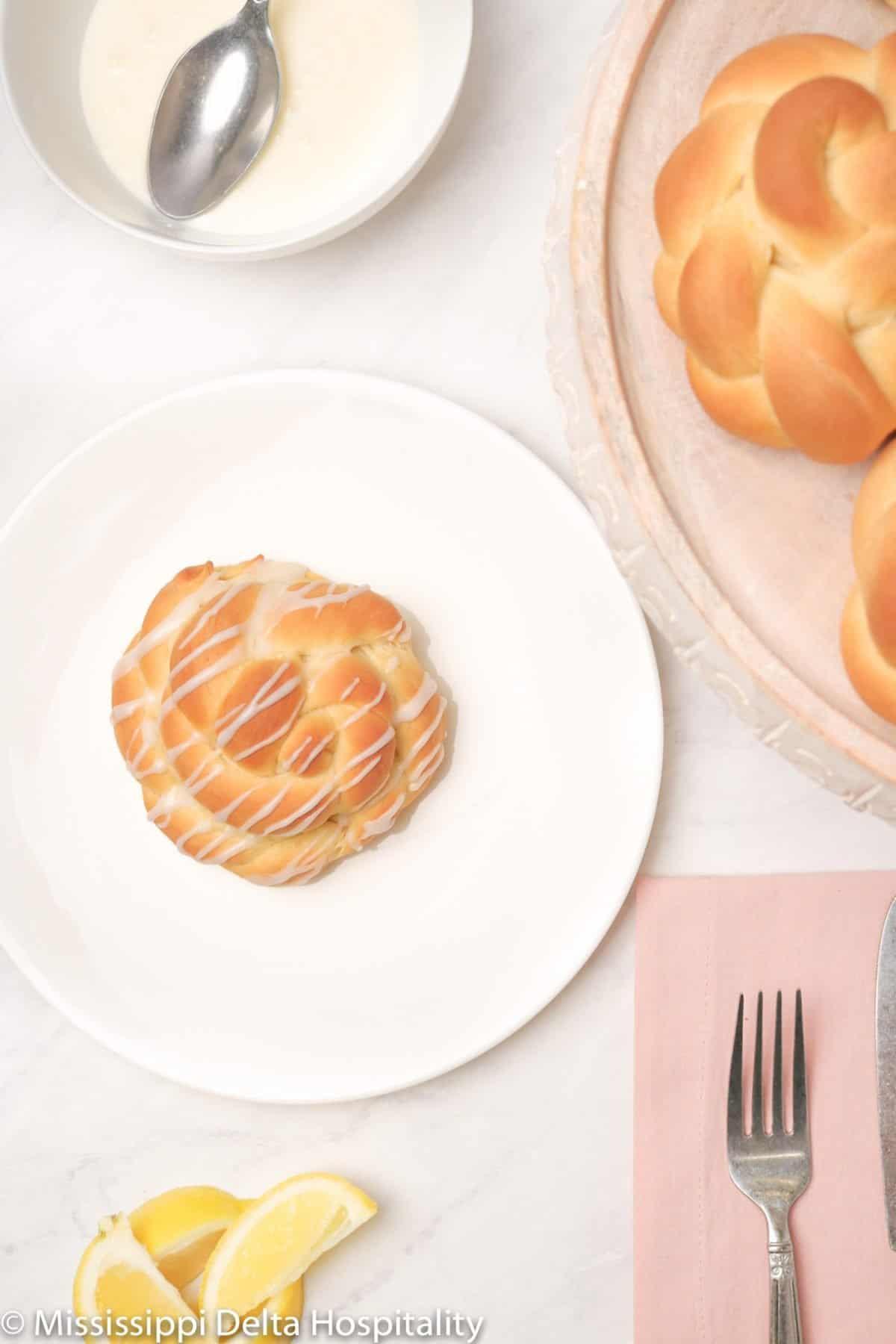 a glazed lemon knot on a white plate with a pink napkin and a fork.