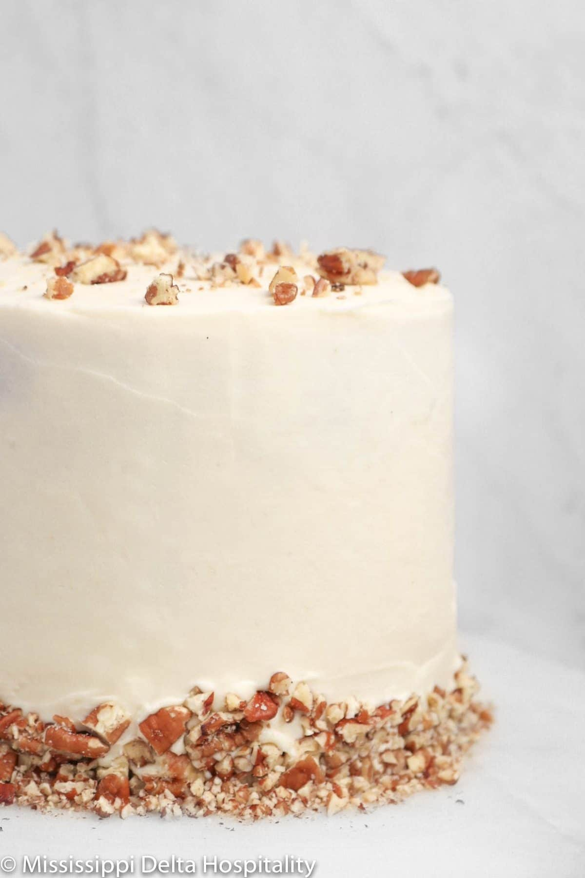 hummingbird cake on a marble cake plate with chopped pecans on top