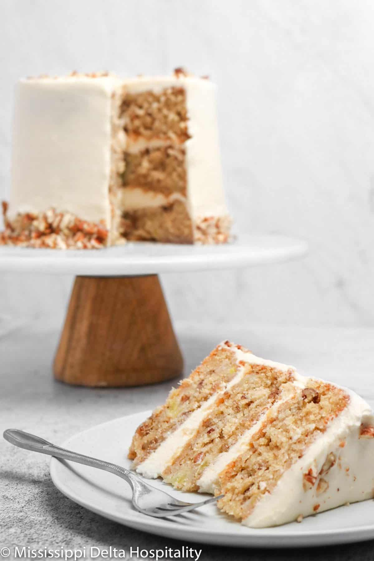 a slice of hummingbird cake on a small plate with the cake in the background