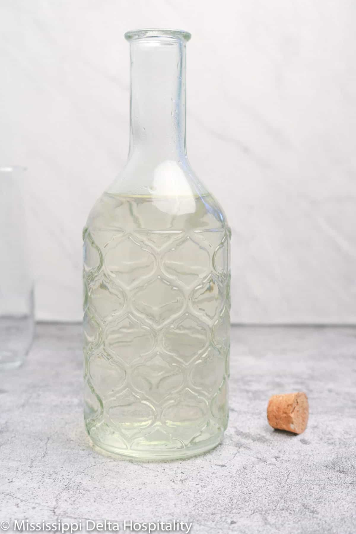 a bottle of simple syrup on a concrete board.