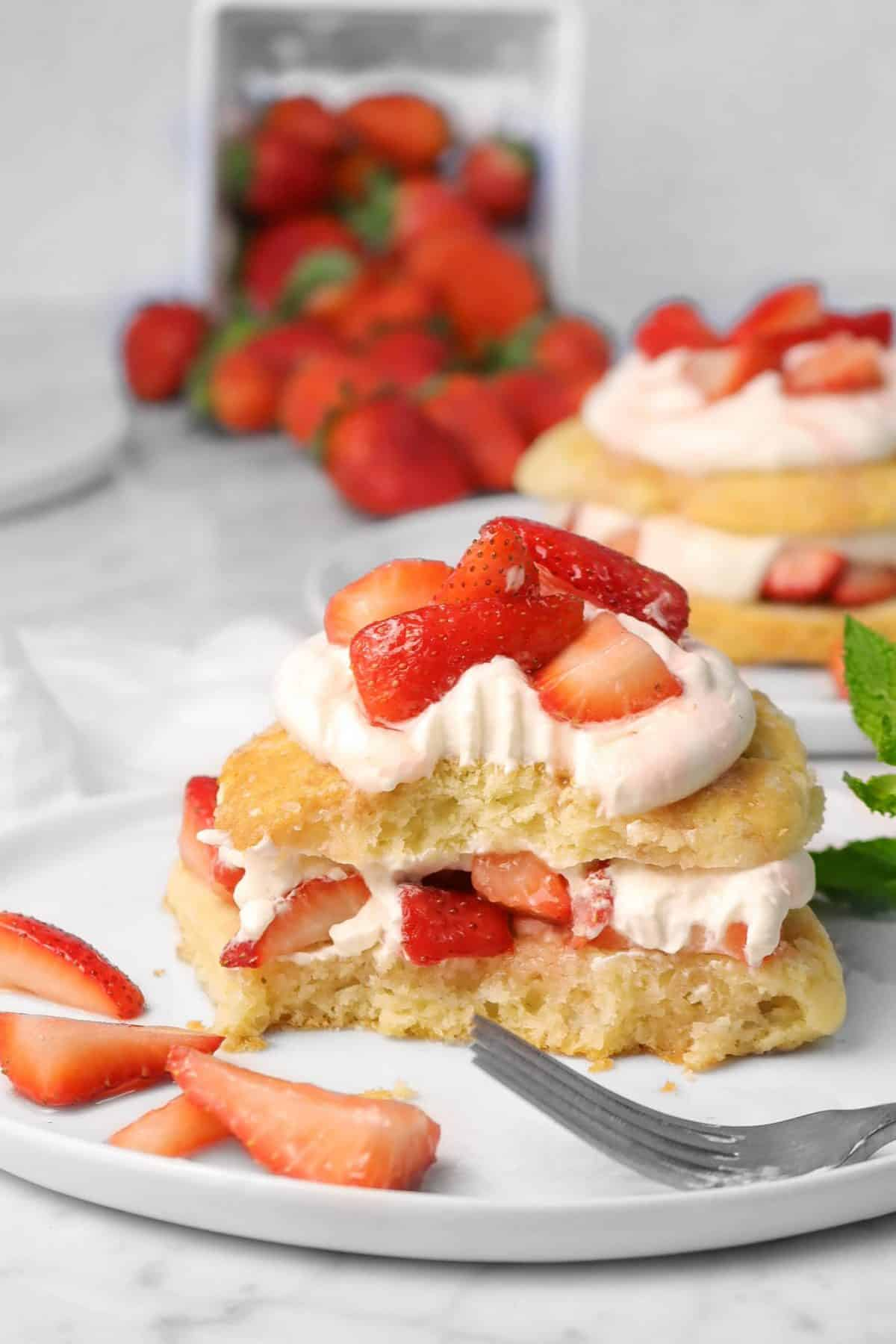 strawberry shortcake with a bite taken out of it and strawberries in the background