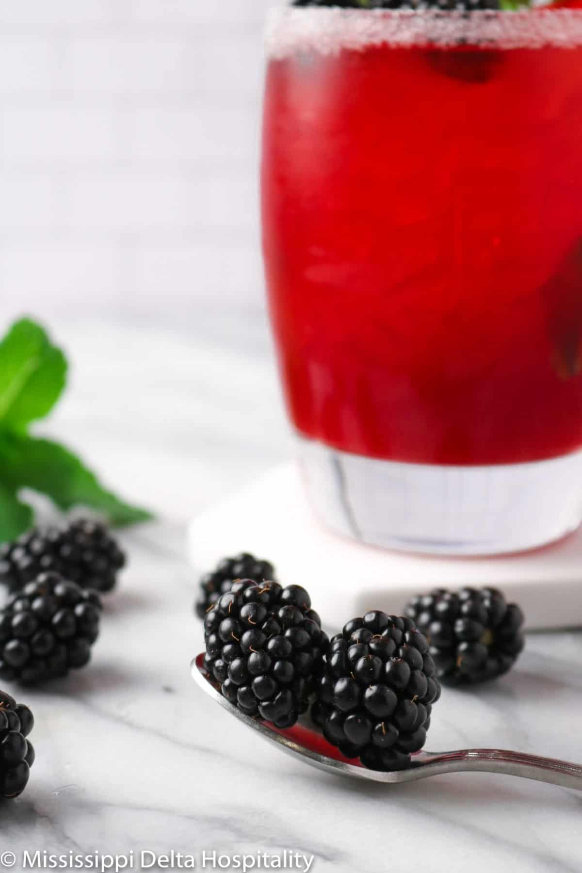 a spoon full of blackberries with a glass of a blackberry bourbon cocktail on a marble board