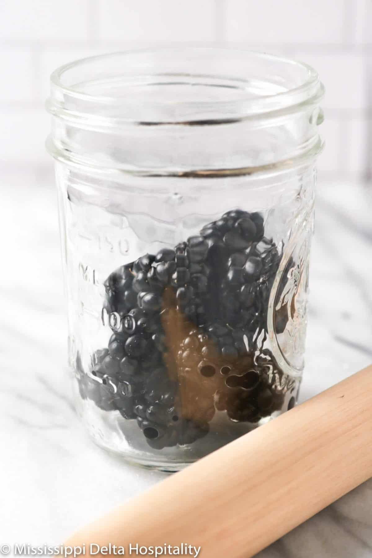a jar halfway full of blackberries on a marble board