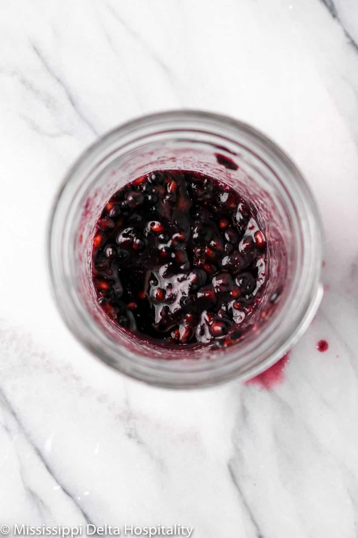 muddled blackberries in a mason jar
