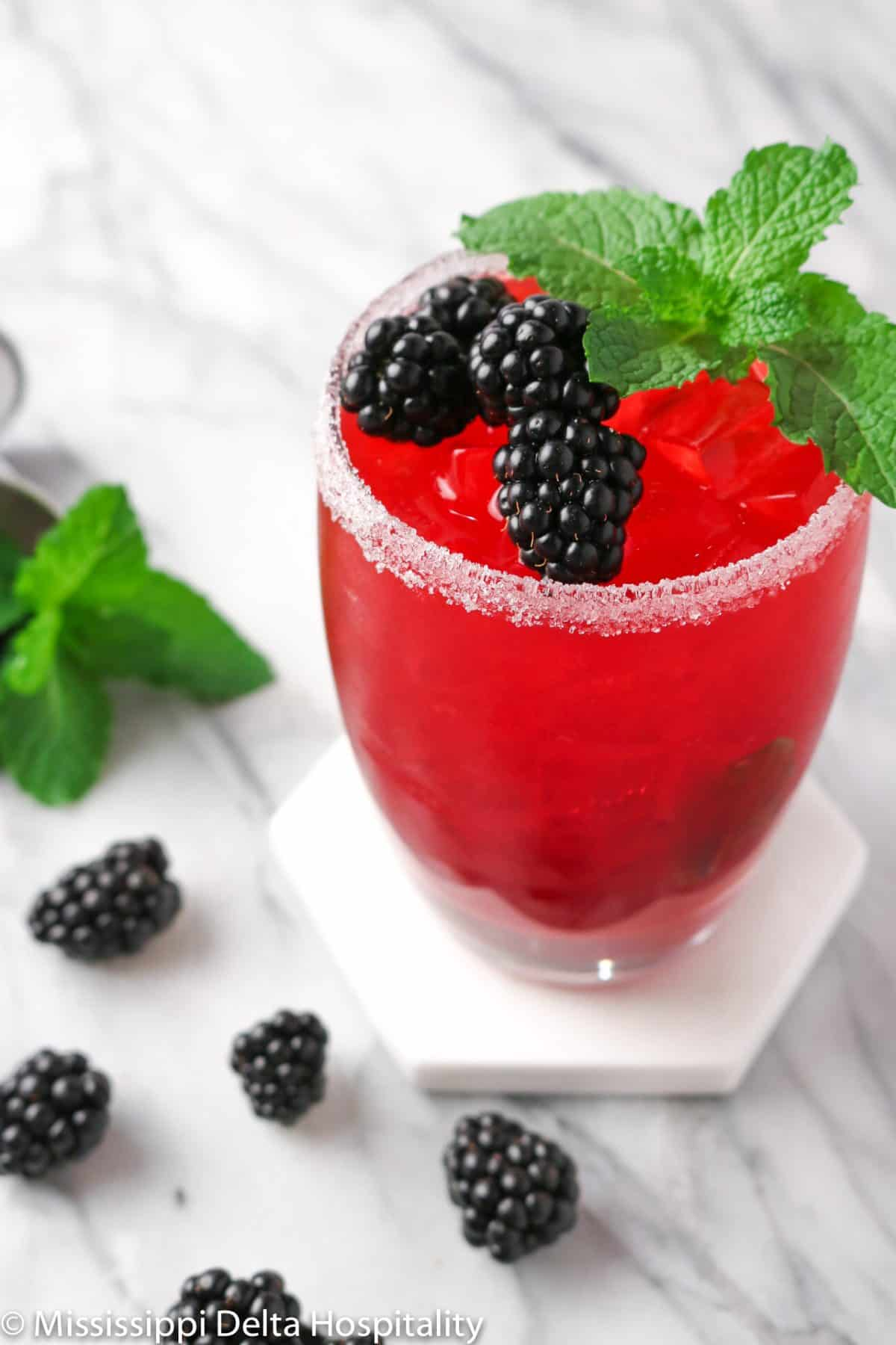 a glass of a blackberry bourbon cocktail with blackberries and mint on a marble board.