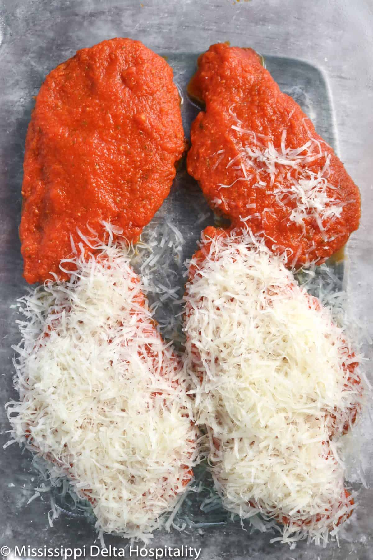 chicken being covered with parmesan cheese