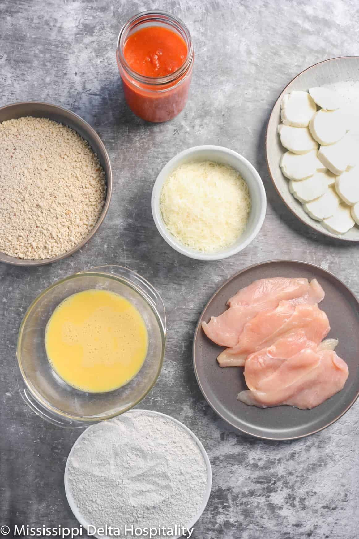 ingredients for chicken parmesan on a concrete board