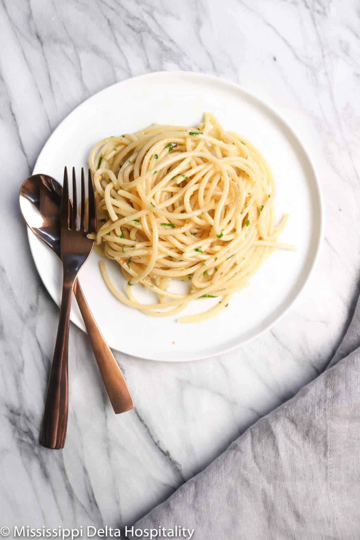 spaghetti aglio e olio on a white plate with a copper spoon and fork and a grey napkin