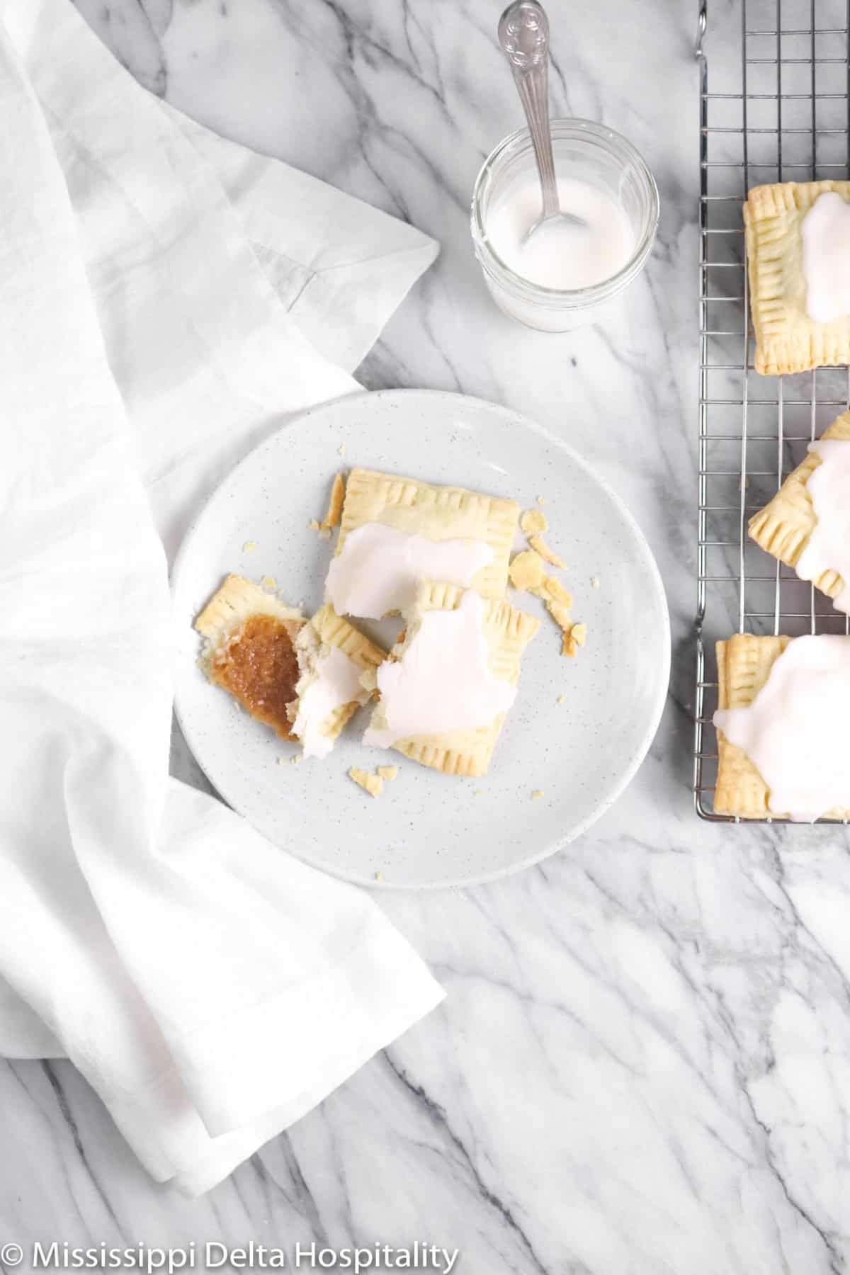 two pop tarts broken up on a plate with a white napkin on a marble board