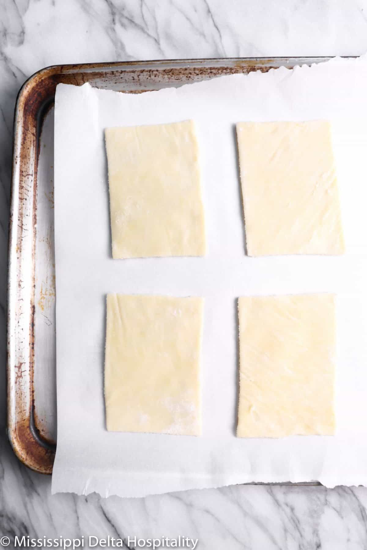 four pieces of pie crust cut into rectangles on a pan