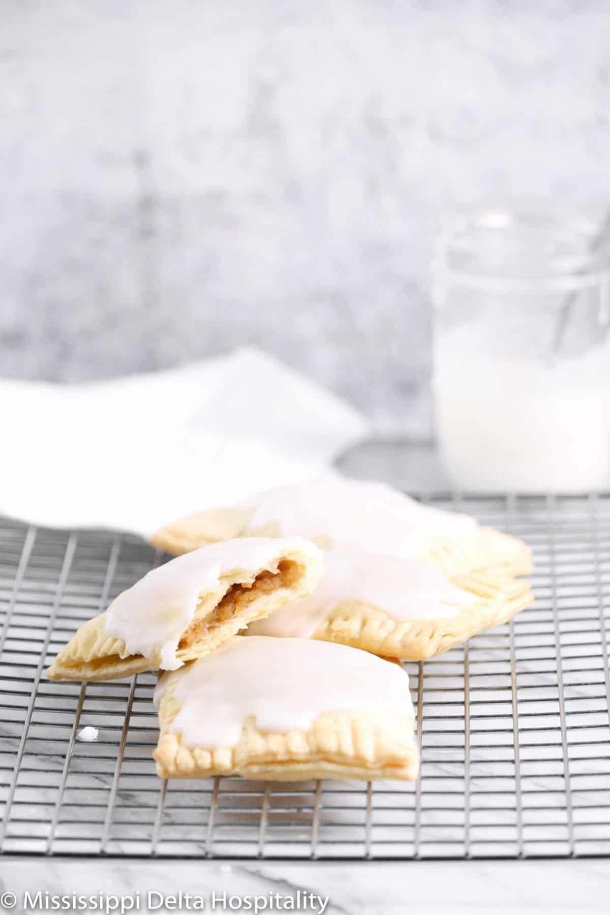 four pop tarts on a cooling rack on a marble board with a white towel and a jar of icing