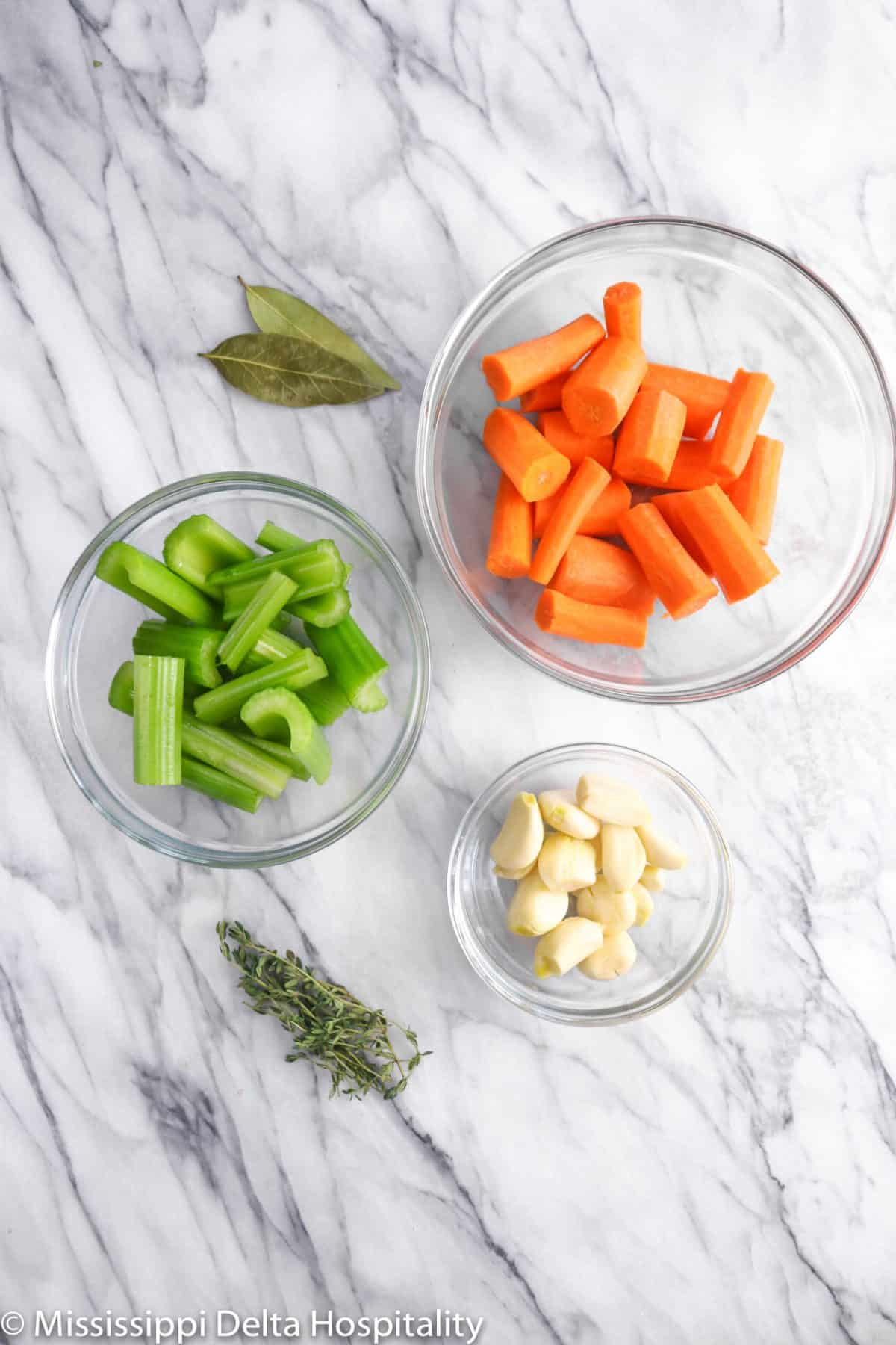 vegetables on a marble board with rosemary and bay leaves