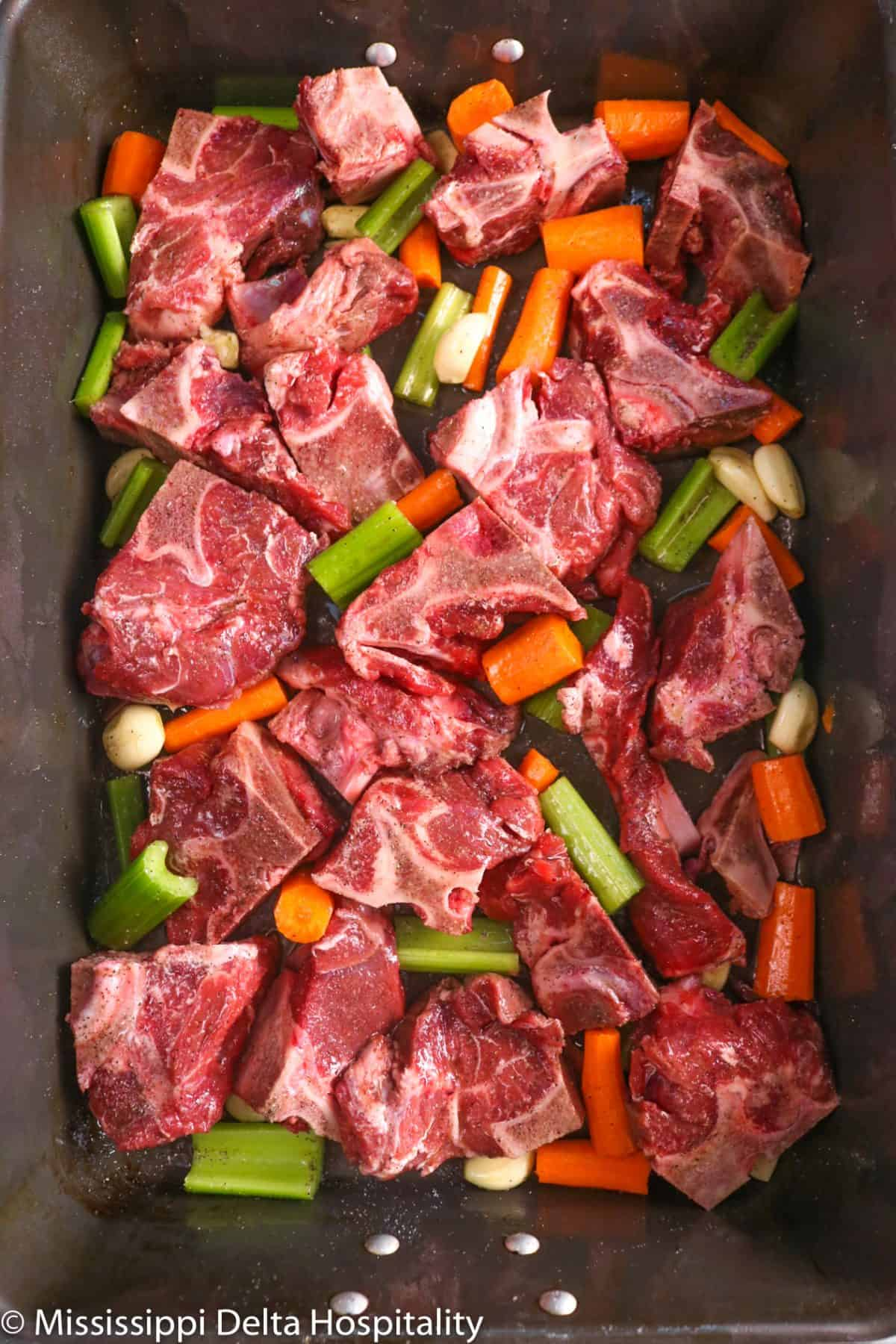 a roasting pan with beef bones and vegetables
