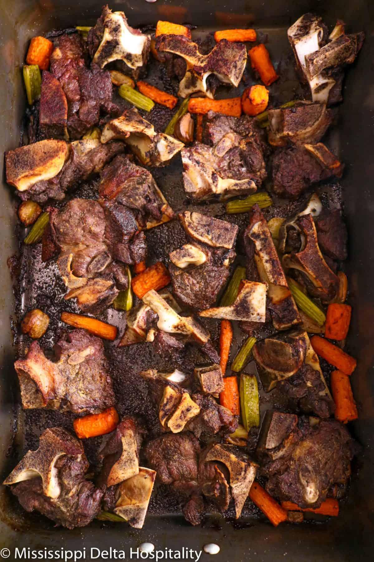 beef bones and vegetables roasted in a roasting pan