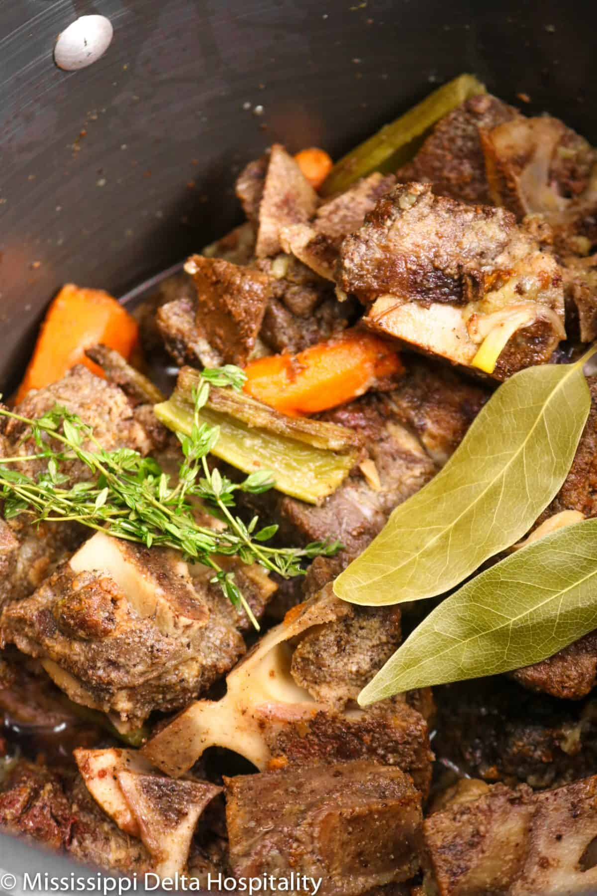 vegetables, beef bones, herbs, and water in a pot