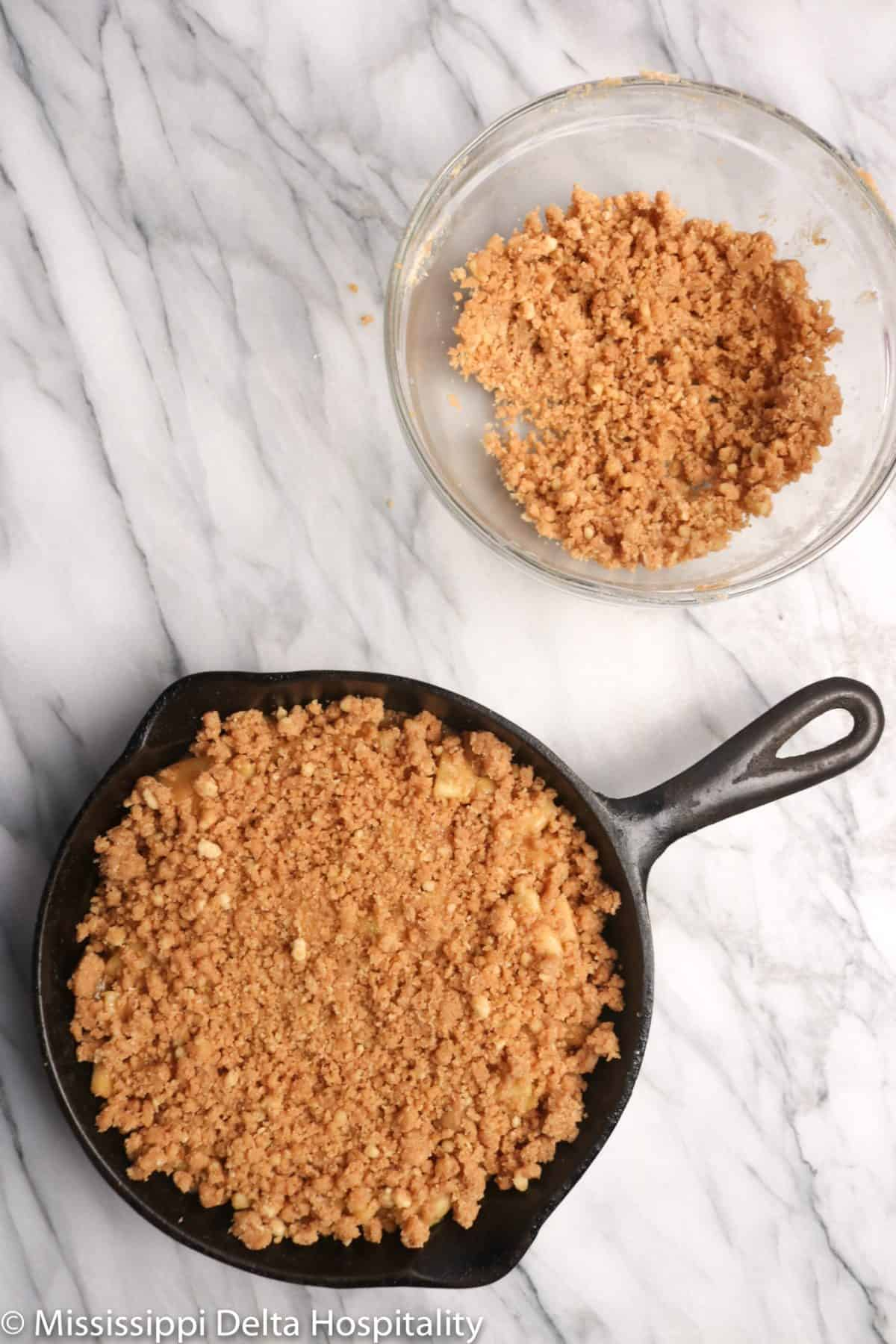a cast iron skillet with apple crumble and streusel in a glass bowl on a marble board