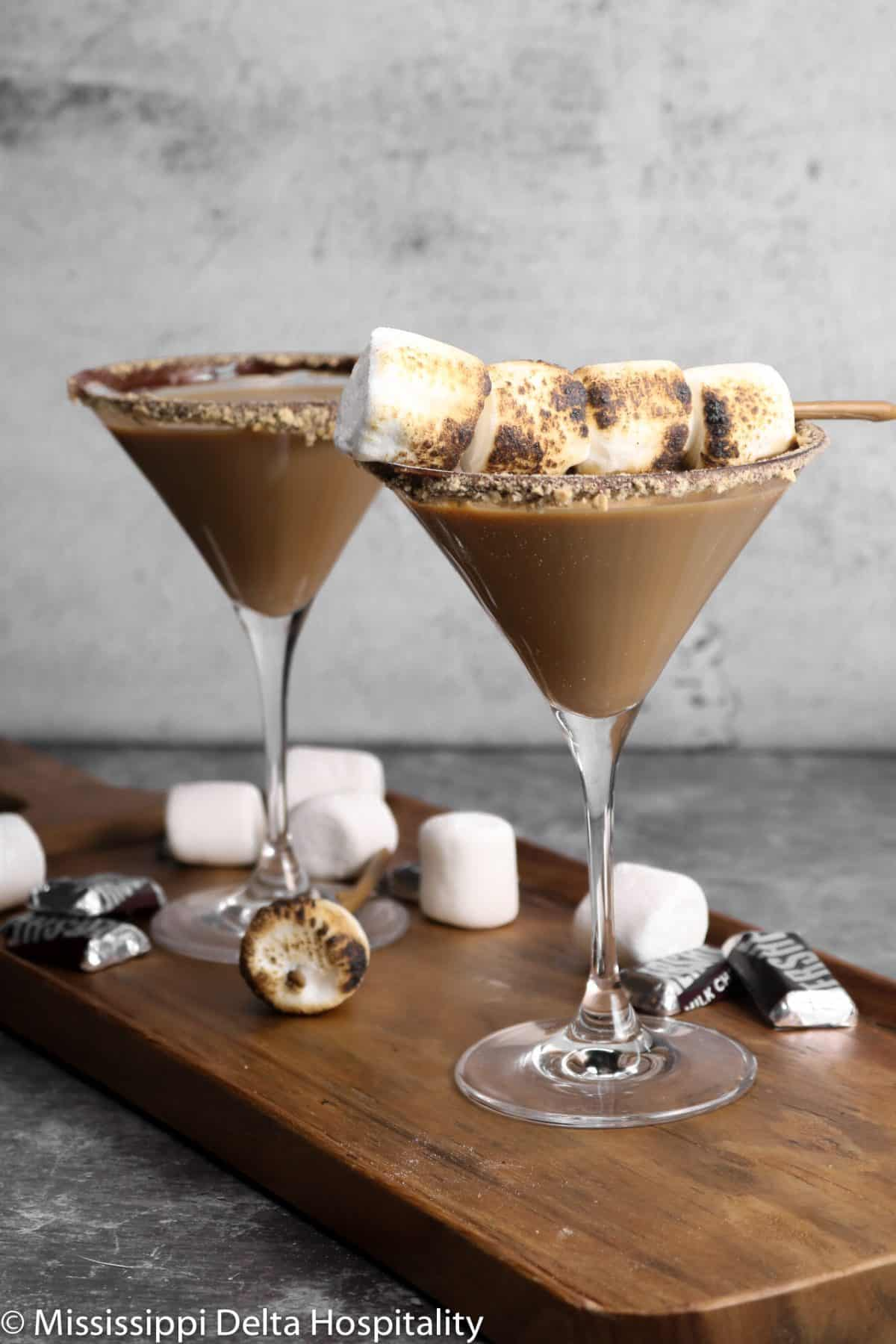 two glasses of s'more martini's on a wood serving board
