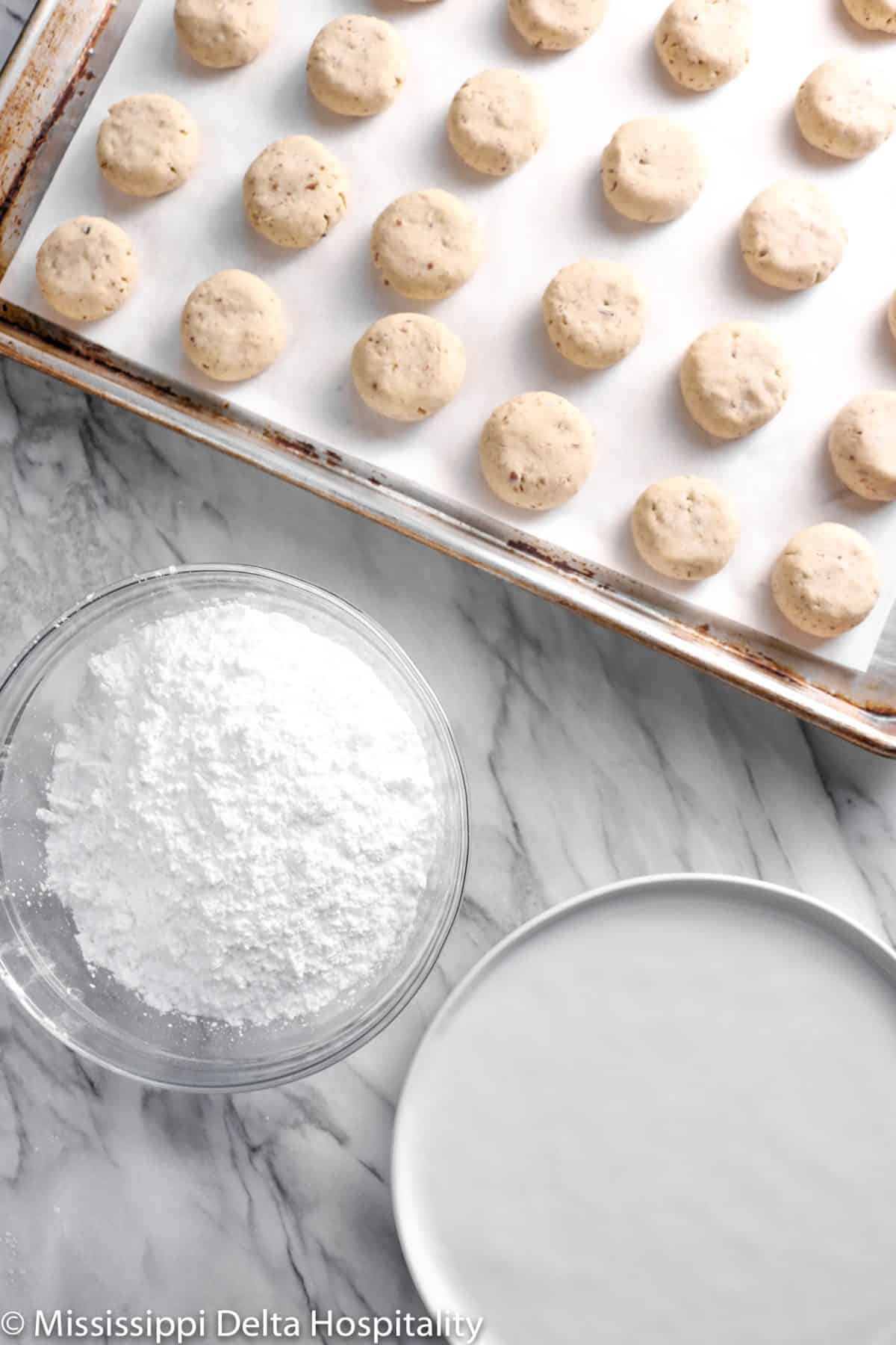danish wedding cookies on a cookie sheet with a bowl of powdered sugar and a plate