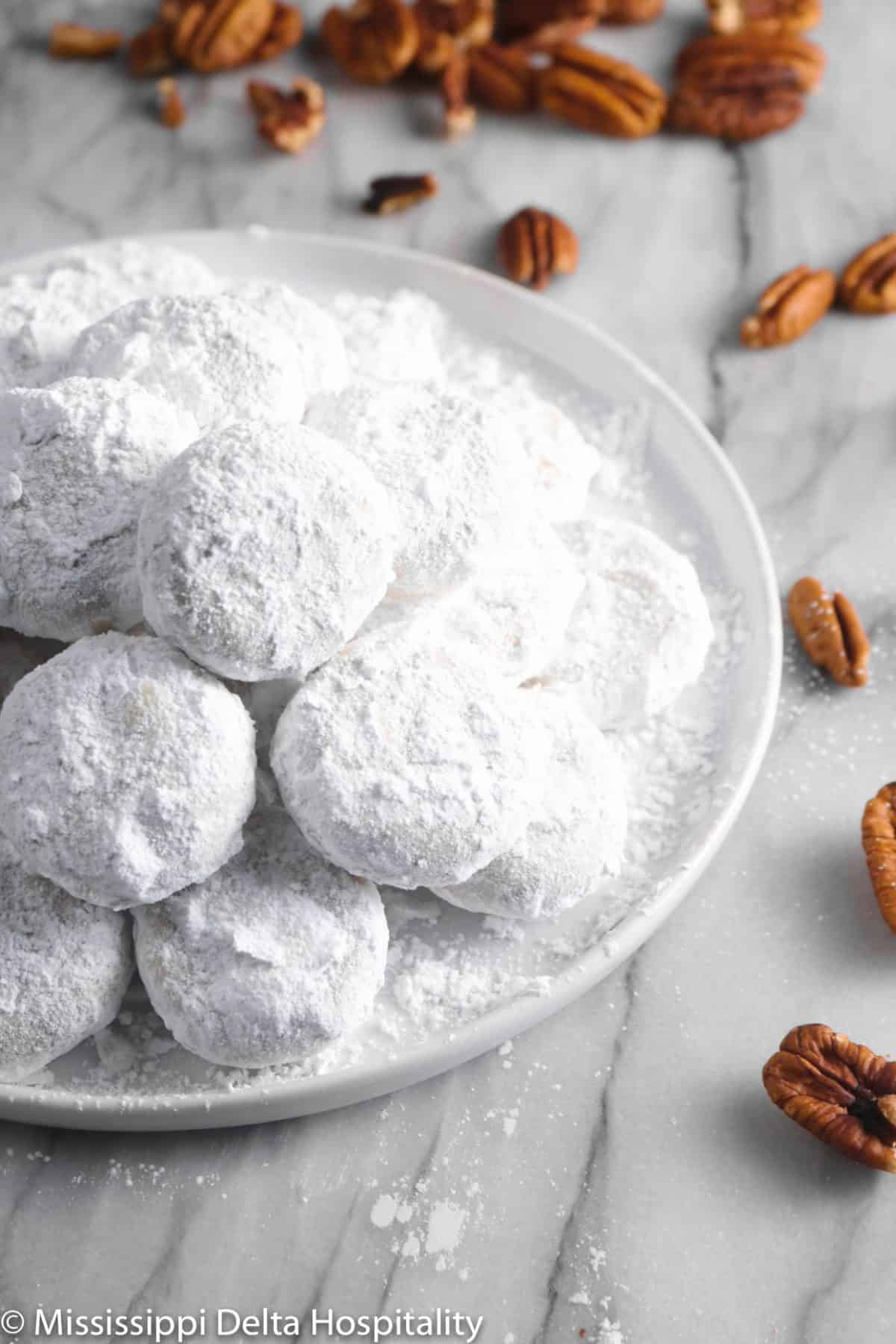 a pile of danish wedding cookies on a white plate