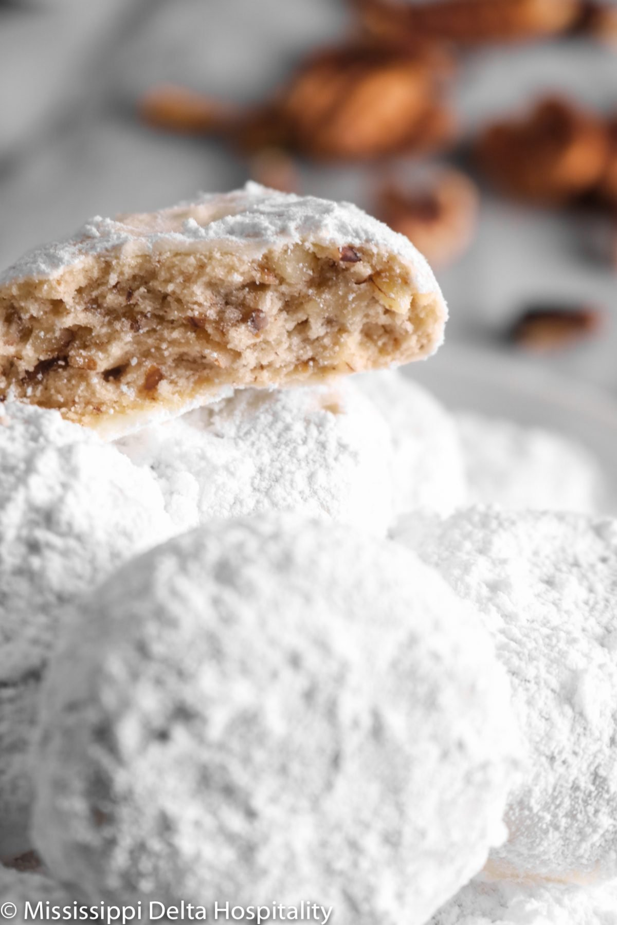 a pile of danish wedding cookies with one broken in half on top