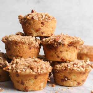 apple cinnamon muffins stacked on each other on a marble board