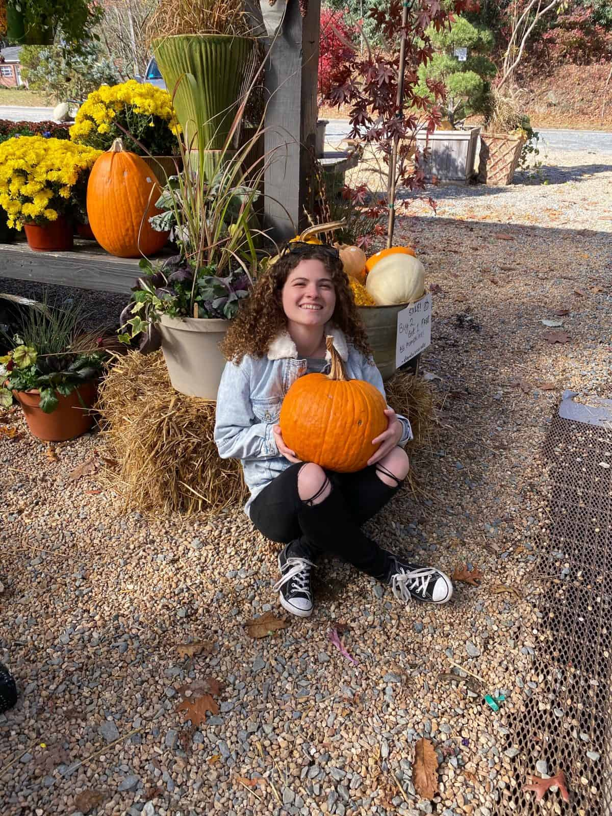 a picture of a girl holding a pumpkin