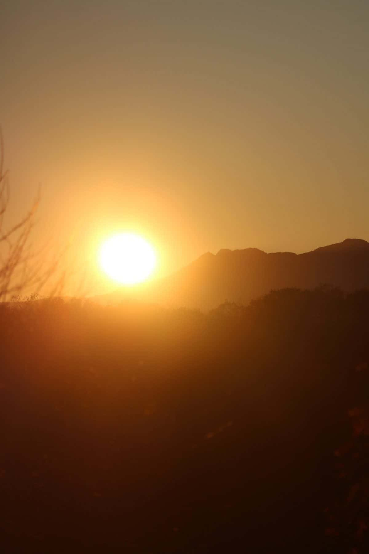 a picture of grandfather mountain with the sun setting behind it