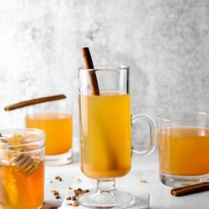 three glasses of spple cider on a concrete board with cinnamon sticks and a jar of honey