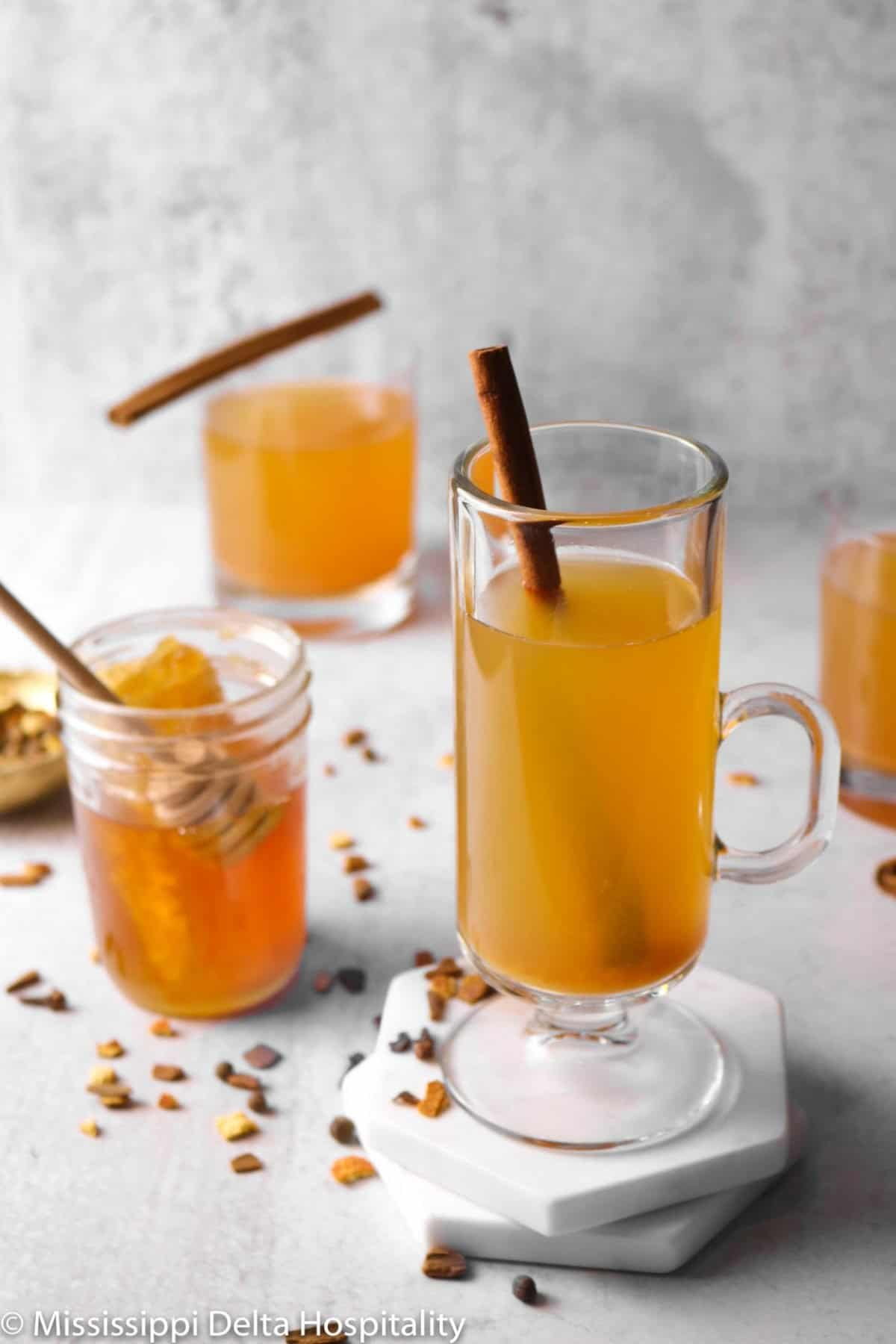 two glasses of cider on a concrete board with a jar of honey