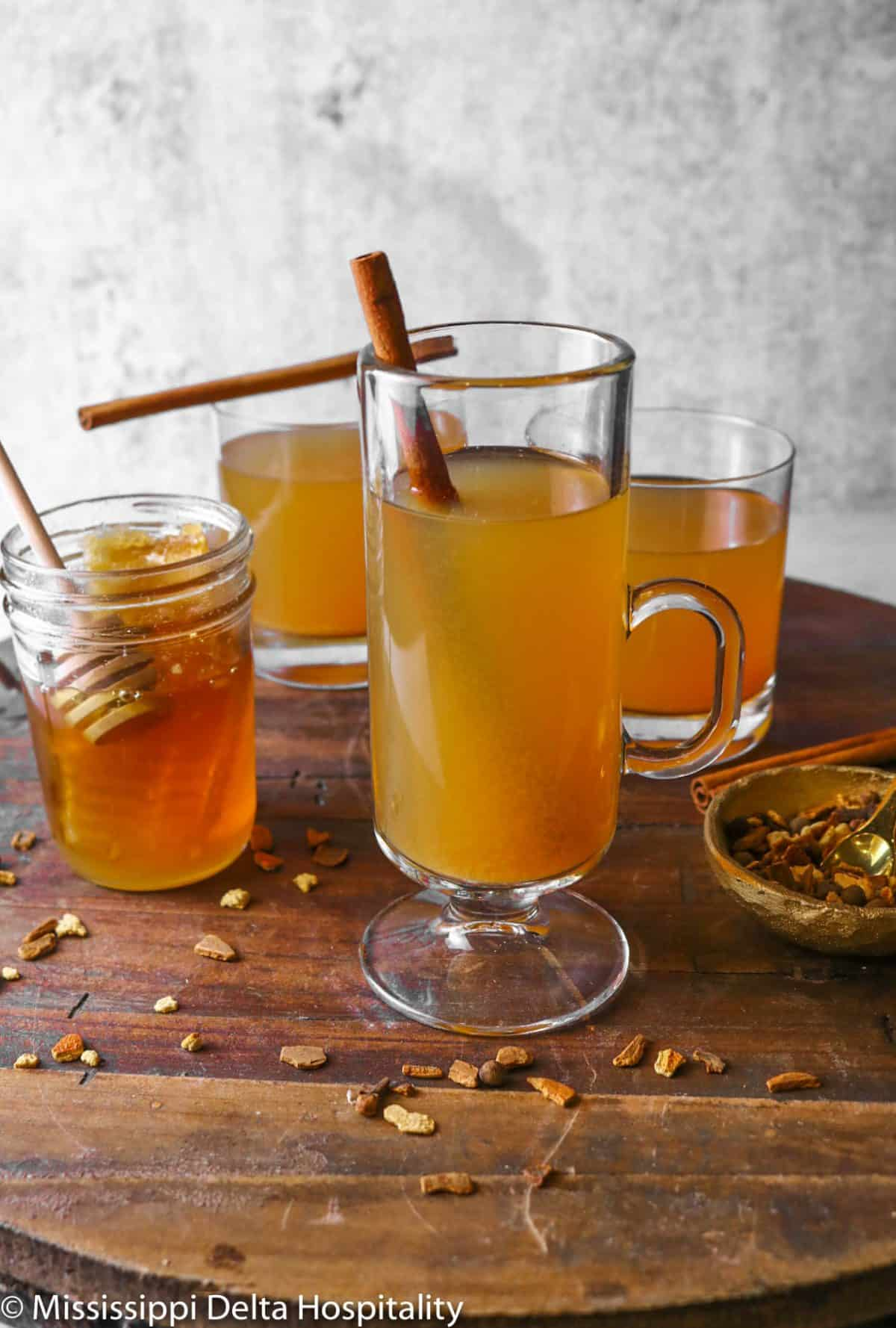 three glasses of apple cider on a wood tray with honey and mulling spices