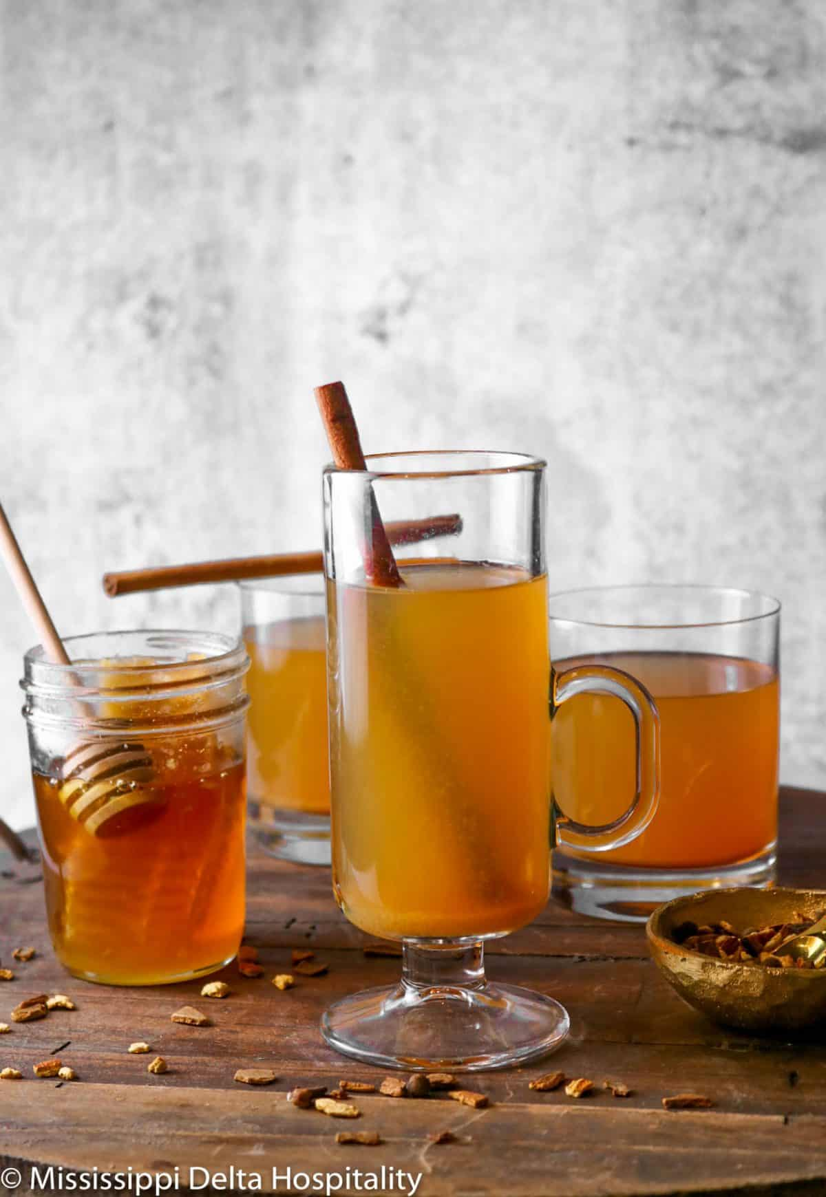three glasses of apple cider on a wood board with a jar of honey and cinnamon sticks