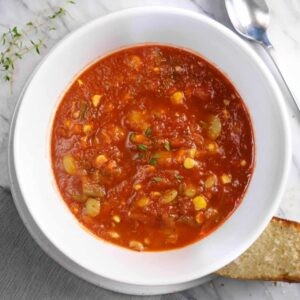 a bowl of vegetable beef soup with thyme, corn bread, a grey napkin, and a spoon on a marble board