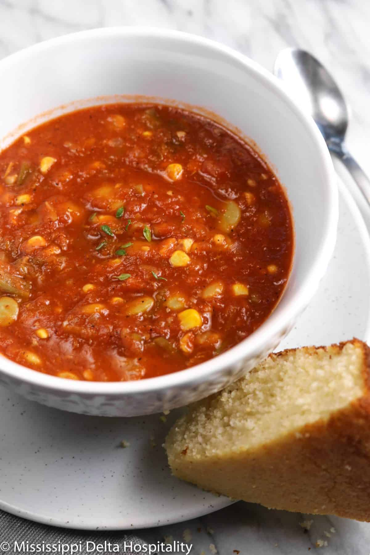 vegetable soup in a white bowl on a small plate with a slice of cornbread