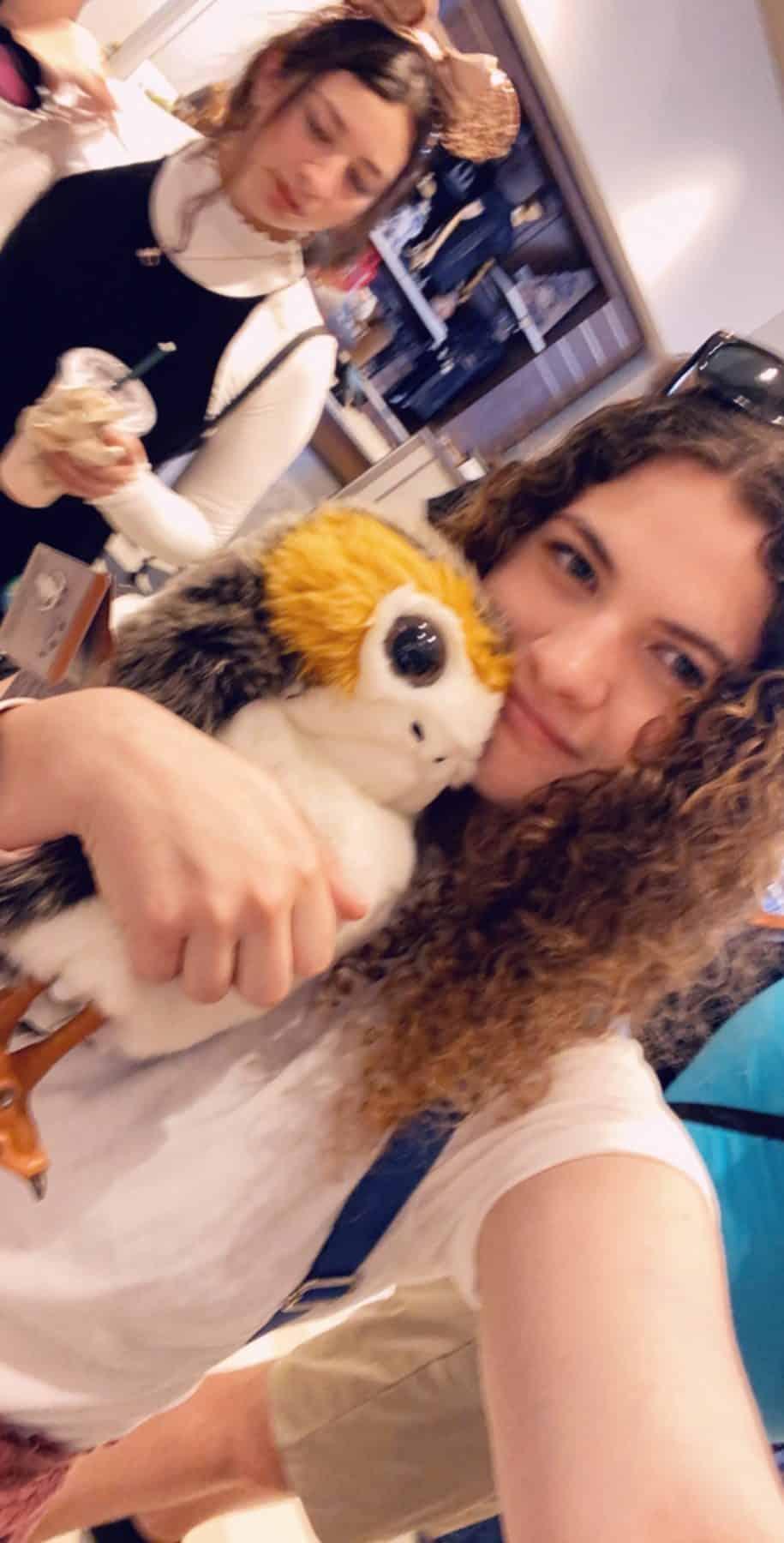 teenage girl hugging a porg stuffed animal