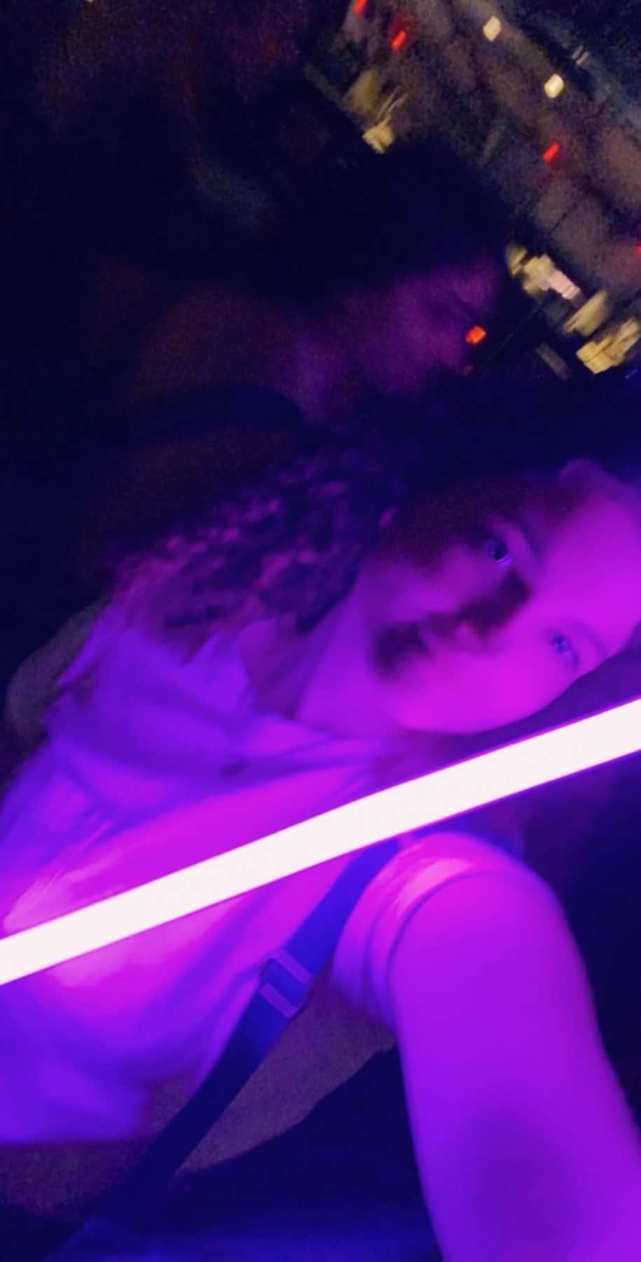 teenage girl holding a purple lightsaber
