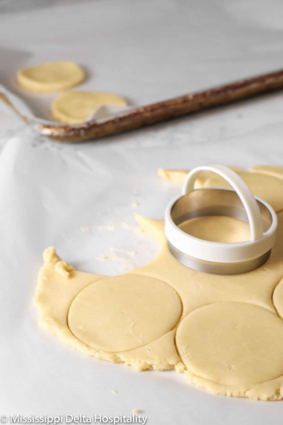 cookies being cut and placed on a sheet pan