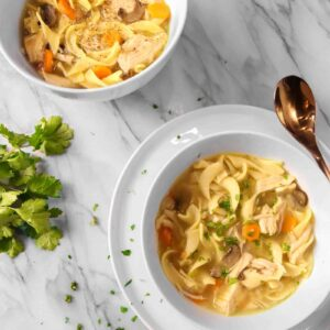 two bowls of chicken noodle soup on a marble board with parsley and a copper spoon