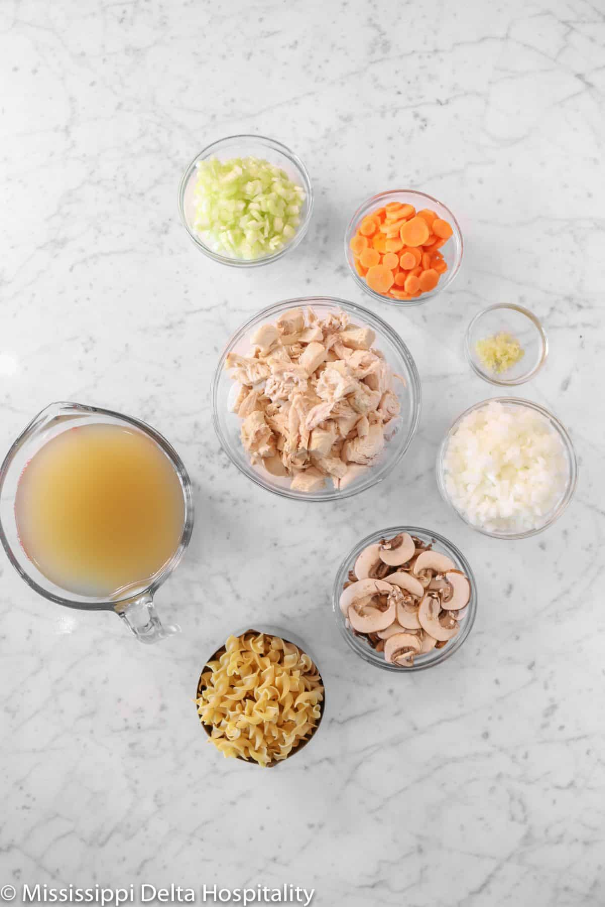 ingredients for chicken noodle soup on a marble board