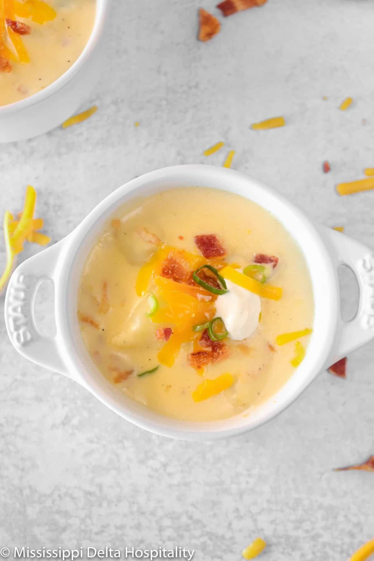 a bowl of baked potato soup on a concrete board with cheddar cheese and bacon sprinkled around