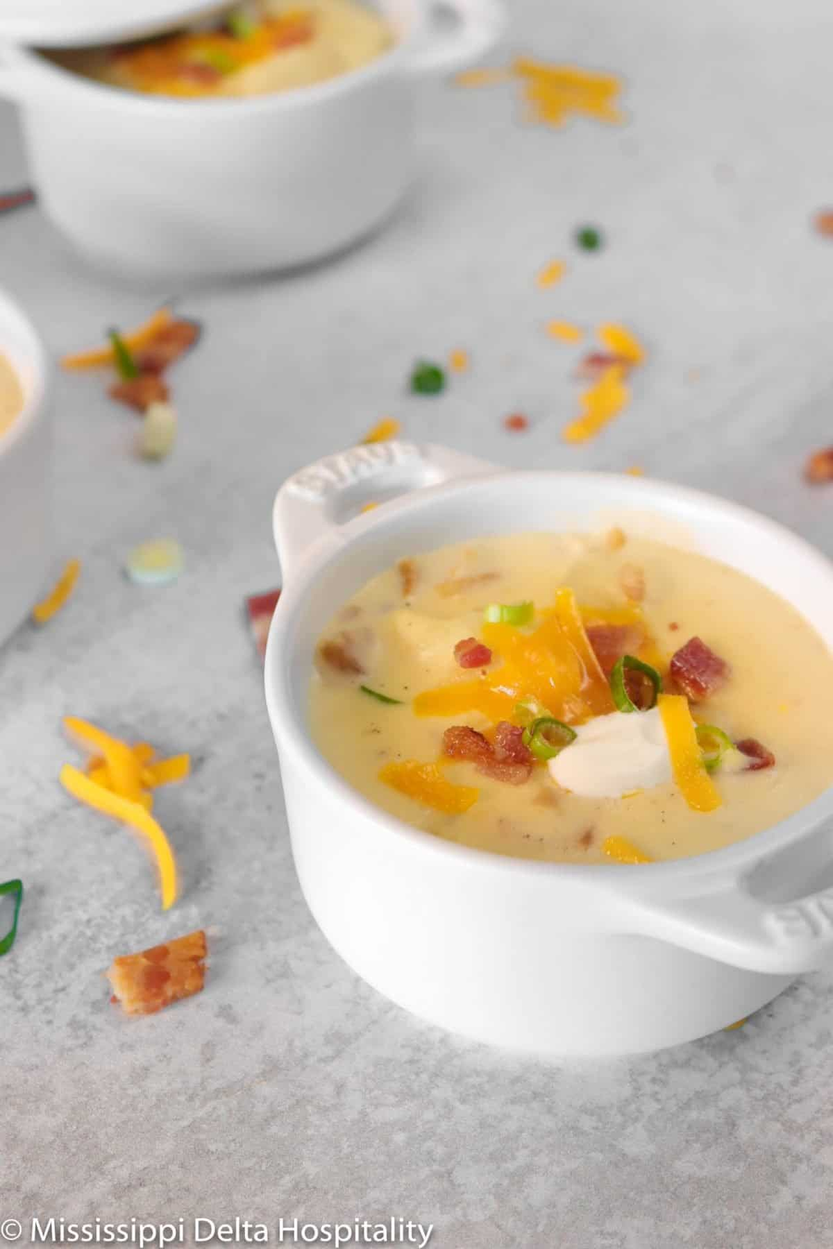 two bowls of baked potato soup on a concrete board with cheddar cheese, green onions, and bacon sprinkled around