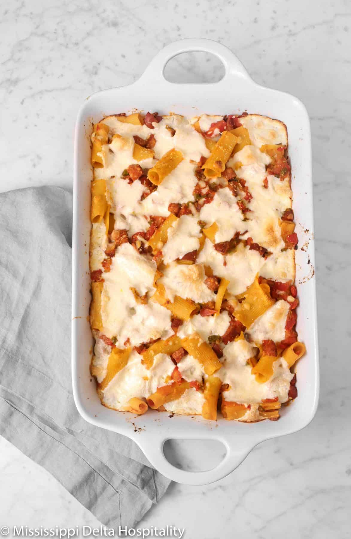 baked rigatoni on a marble board with a grey napkin