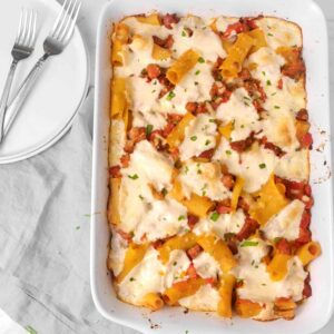 baked rigatoni on a marble board with two plates, two forks, a grey napkin, and basil leaves